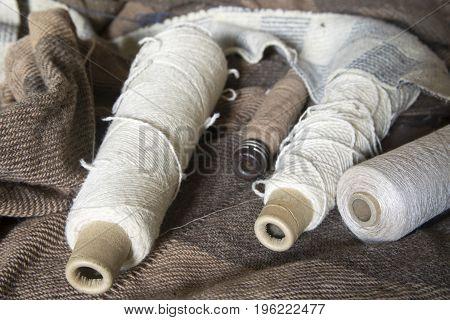 Bobbins of yarn on wool woven blankets.