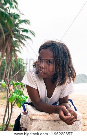 EL NIDO PALAWAN PHILIPPINES - JANUARY 20 2017: Vertical perspective of Filipino girl leaning against a styrofoam box at Nacpan Beach Philippines.