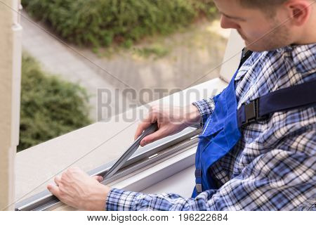 Close-up Of A Repairman's Hand Fixing Window