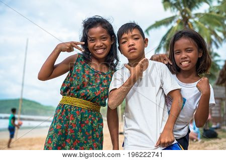 EL NIDO PALAWAN PHILIPPINES - JANUARY 20 2017: Horizontal picture of filipino trio posing to the camera at Nacpan Beach Philippines.