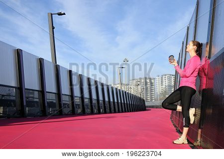 Young Woman Having A Coffee Break On A Bright Pink Road
