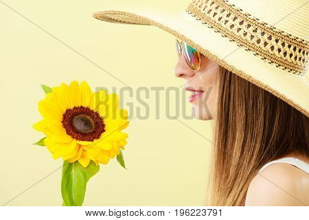 Closeup side view of attractive summer woman in sunglasses straw hat with sunflower in her hand on yellow background