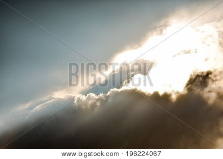 A bright opening in dark storm clouds with sun glare.