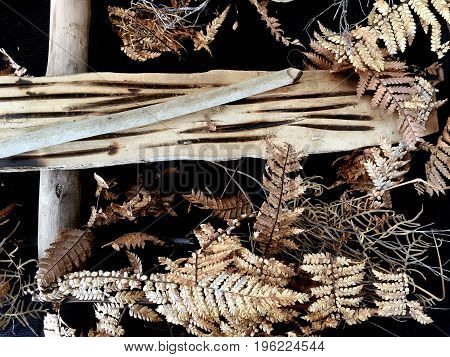 Survival fire making craft dried leaves and wood background.