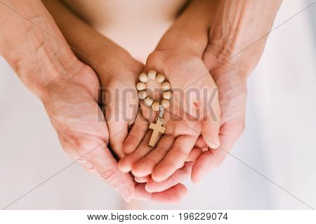 Christian chotki in the hands of mother and child. Mother's arms embrace the baby's hands