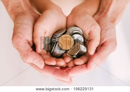 Coins in the hands of mother and child. Mother's arms embrace the baby's hands