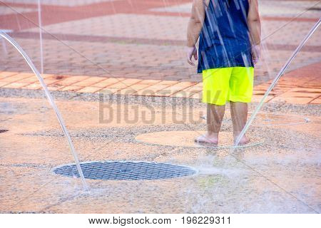young child playing in city splash pad