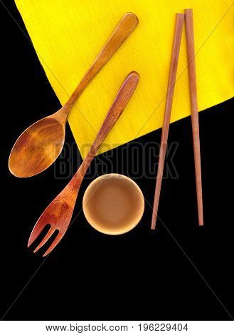 Wooden Cutlery on a bright yellow linen napkin isolated on black background. Free space for text.