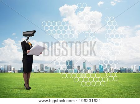 Elegant businesswoman outdoors with camera instead of head and media interface on screen