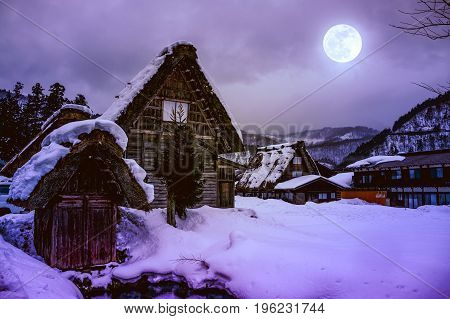 Snow Covered The Ground In Winter. Town With Night Sky And Full Moon.