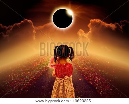 Amazing scientific natural phenomenon. Total solar eclipse glowing above child on pathway with night sky and clouds. Full solar eclipse is photo realistic illustration. Sepia tone.
