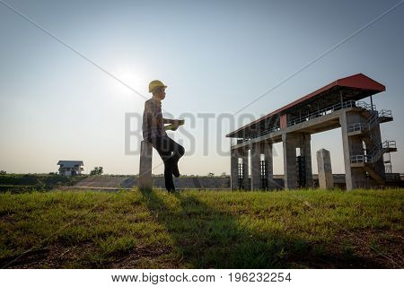 Male Employee Holds A File While Looking At A Public Floodgate.