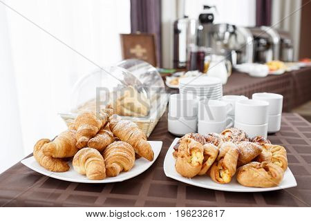 Breakfast at the hotel. Buffet Table with dishware waiting for guests. croissants and puff in the foreground. Coffee machine. Selective focus