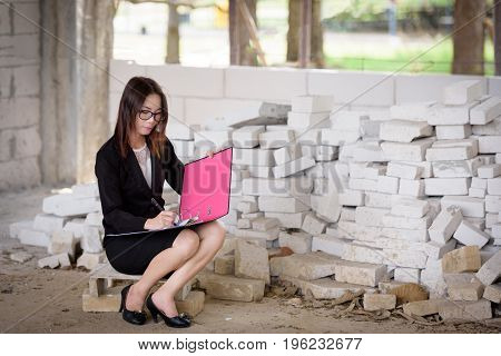 The Hand Of A Businesswoman Is Writing A Report While Sitting In A Brick Building.