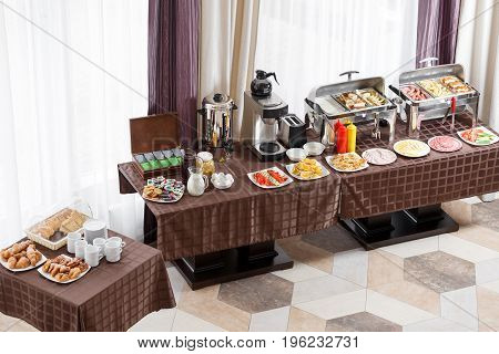 Breakfast at the hotel. Buffet Table with dishware waiting for guests. hot meals, vegetables, fruits, meats, cheeses. Coffee machine.