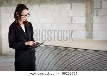 The Hand Of A Businesswoman Is Pressing A Calculator Counting  In A Building.