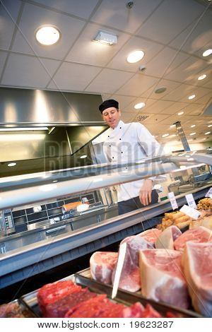 A butcher looking at a fresh meat counter in a grocery store
