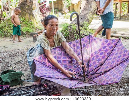 Rakhine State Myanmar - October 14 2014: Umbrella repair woman in a village along the Lemro River in the Rakhine State of Myanmar. Most places in Myanmar getting a broken umbrella repaired is not a problem.