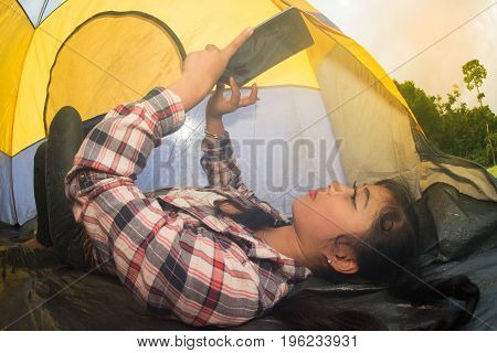 Beautiful smiling Asian woman lying down and looking tablet at entrance of a blue - yellow camping tent.