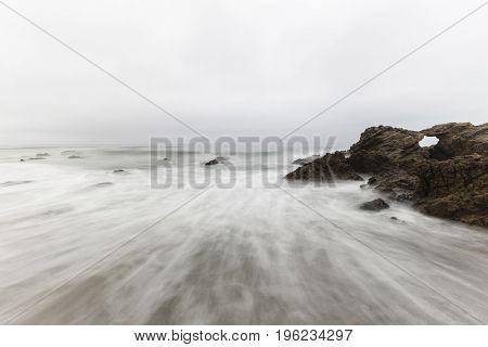 Rocky Leo Carrillo State Beach with motion blur water in Malibu, California.
