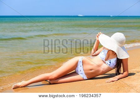 Woman in big straw sunhat and red pareo sunbathing on a sandy beach. Summer holidays concept