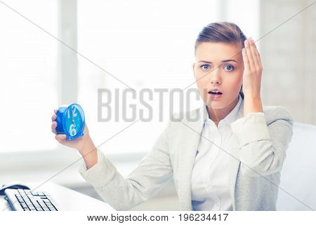 picture of stressed businesswoman holding clock