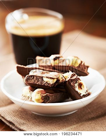 Pieces of Milk Chocolate with Hazelnuts and a Glass of Coffee
