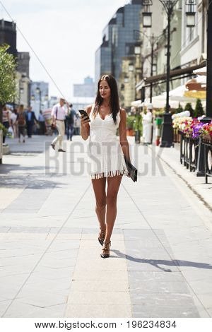 Portrait in full growth, beautiful young brunette woman in white dress, summer outdoors