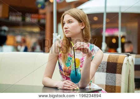 Young brunette woman drinking cocktail in a cafe indoors