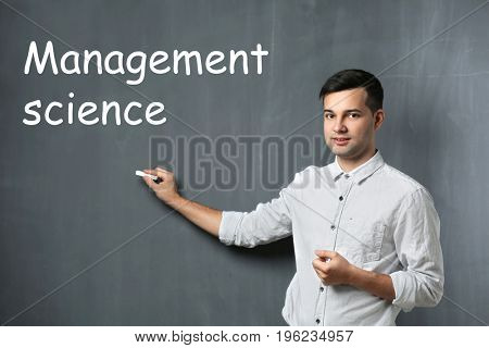 Concept of management science. Young man with piece of chalk on gray background