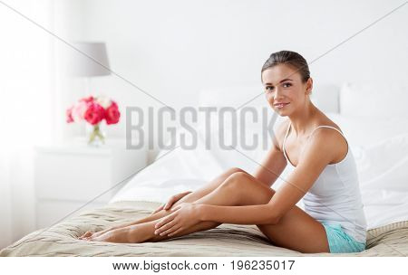 people, beauty, depilation, epilation and bodycare concept - beautiful woman touching smooth leg skin on bed at home bedroom poster