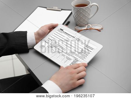 Man using tablet for filling in individual income tax return form at table