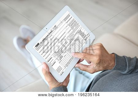 Senior man using tablet for filling in individual income tax return form, closeup