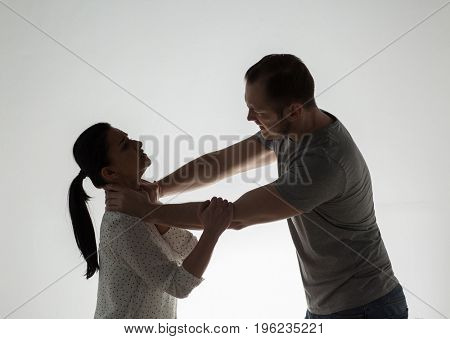 domestic violence, people and abuse concept - couple having fight and man choking woman