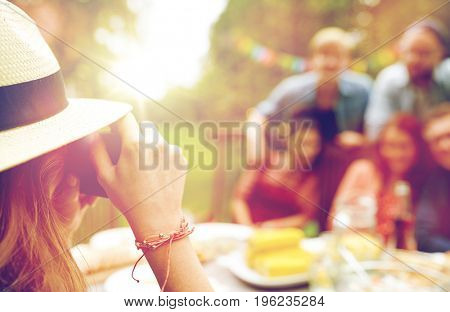 leisure, holidays and people concept - happy friends having dinner and photographing at summer garden party