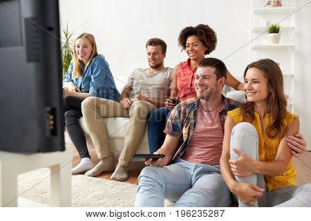 friendship, leisure, people and entertainment concept - happy friends with remote control and drinks watching tv at home