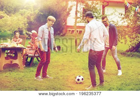 leisure, holidays, people and sport concept - happy friends playing football at summer garden party