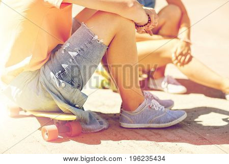 summer holidays, extreme sport and people concept - close up of teenage couple with short modern cruiser skateboards on city street
