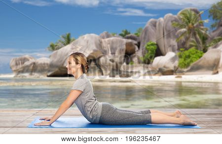 fitness, sport and people concept - woman doing yoga in dog pose on mat over exotic tropical beach background