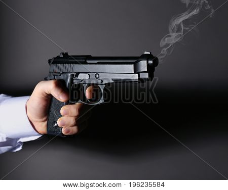 Man holding smoking gun on dark background