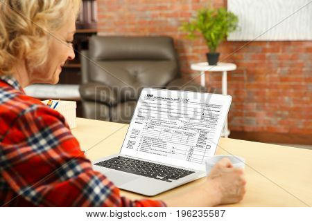 Senior woman using laptop for filling in individual income tax return form at table