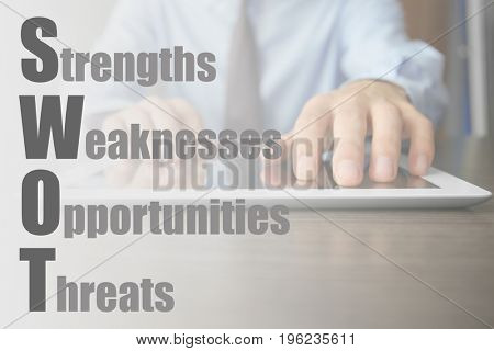 Management concept. Businessman using tablet at table, closeup