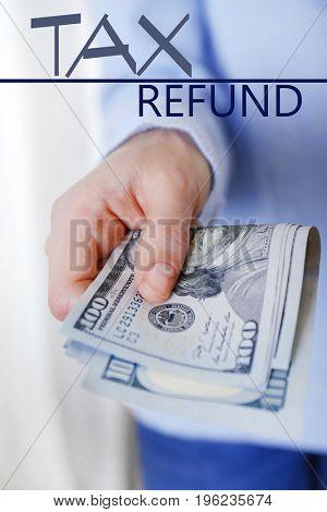 Man holding money, closeup. Tax refund concept