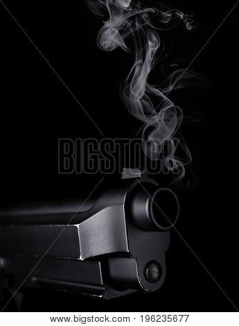 Smoking gun on black background, closeup