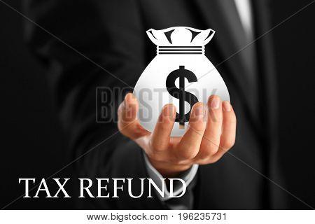 Businessman holding money bag, closeup. Tax refund concept