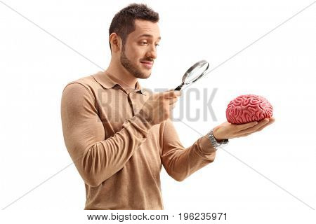 Young guy examining a brain model with a magnifying glass isolated on white background