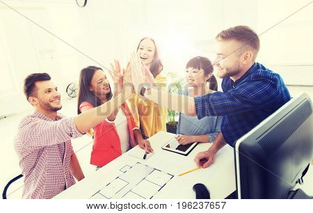 business, startup, architecture, gesture and people concept - happy international creative architect team or students with blueprint making high five at office