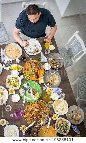 Man sitting on the table with food leftovers top view