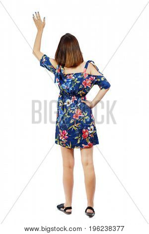 Back view of beautiful woman welcomes. Young teenager girl in dress hand waving from. Rear view  people collection.  Isolated over white background. A girl in a dress in a flower meets someone