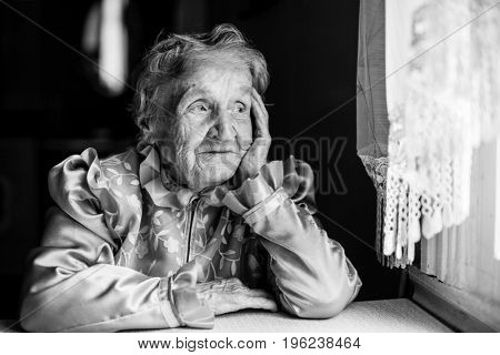 An elderly woman in ethnic clothing, black-and-white photo.